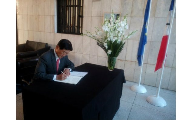 The Ambassador of South Korea signing the condolence book at the French Embassy