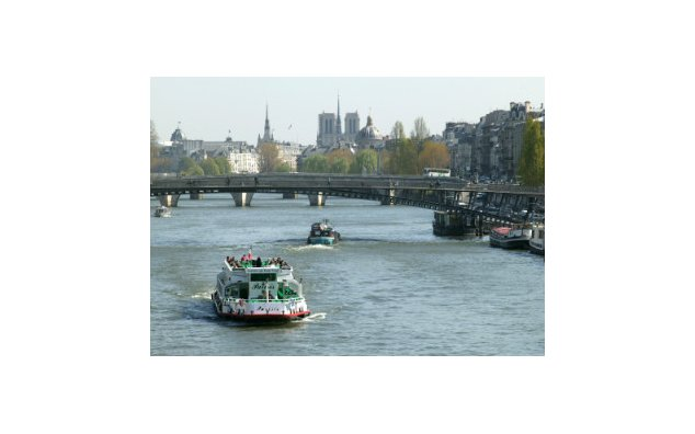 A « bateau-mouche » cruising boat and barges on the Seine River in Paris. Notre Dame Cathedral and Institut de France © (...)