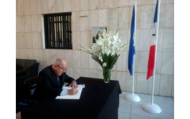 The ambassador of Cuba to Pakistan signing the condolence book at the French Embassy