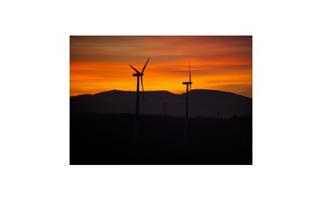 Silhouette of wind-powered generators against the evening sky