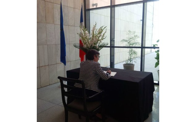 The Ambassador of Australia sign the condolence book at the French Embassy