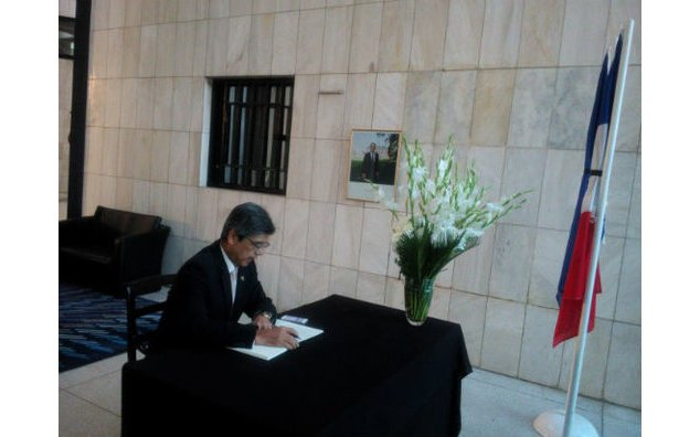 The Ambassador of Japan to Pakistan signing the condolence book at the French Embassy